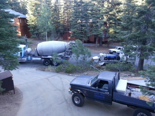 Cement truck and pump truck setting up to get cement to the garage area