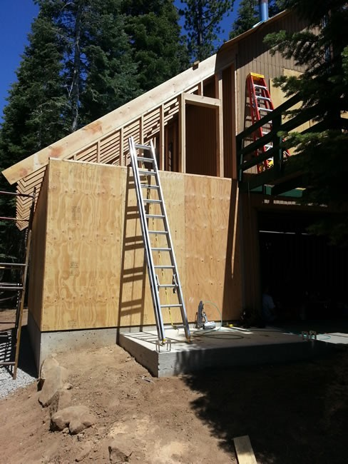 Shear wall put up around the garage.  Doorway framed for storage entrance from the deck.  Rafters in place!